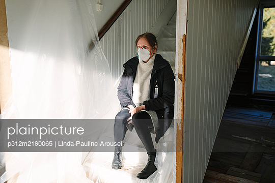 Woman wearing protective mask on staircase - p312m2190065 by Linda-Pauline Arousell