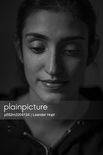 Portrait of young woman at twilight - p552m2204134 by Leander Hopf