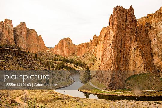 Stream through sheer cliffs in desert landscape, Smith Rock State Park, Oregon, United States - p555m1412143 by Adam Hester