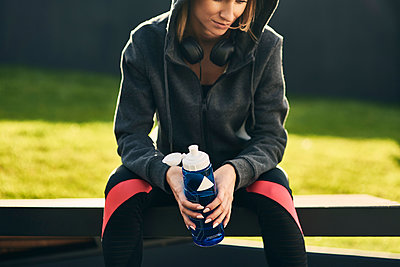 Woman taking a break after workout, holding drinking bottle - p300m2159852 by gpointstudio