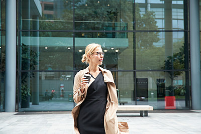 Woman holding coffee cup while standing against office building - p300m2227076 by Pete Muller