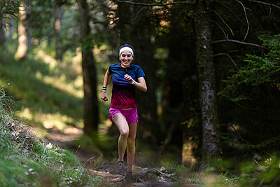 Female athlete running on trail in forest - p300m2282422 by Mikel Taboada