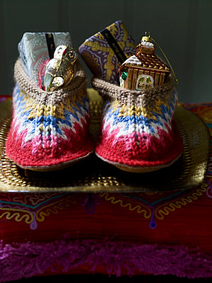 Gift wrapped presents and baubles in pair of woollen slippers - p349m2167789 by Polly Wreford