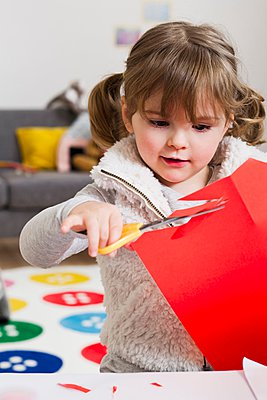 Girl cutting coloured card at home - p429m1024339f by Emely