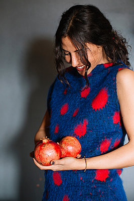 Young woman in red patterned dress holding pomegranates - p429m2051933 by Alberto Bogo