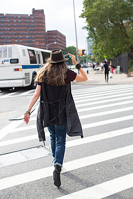 Stylish mature woman wearing trilby strolling over suburban pedestrian crossing, rear view - p924m2074549 by Sioux Nesi