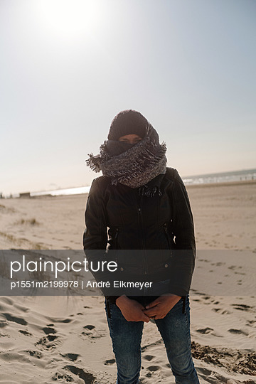 Woman with cap and scarf on the beach - p1551m2199978 by André Eikmeyer