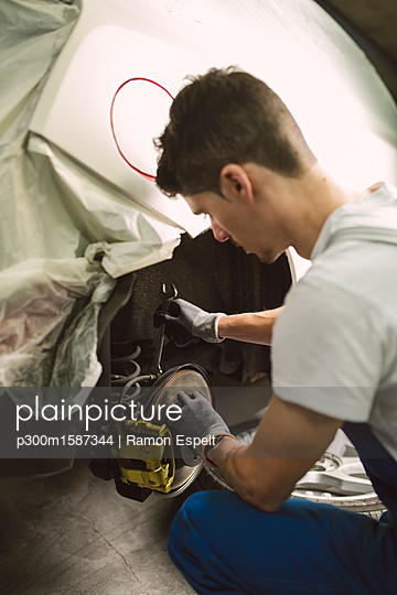Mechanic fixing the brake caliper of a car in a workshop - p300m1587344 von Ramon Espelt