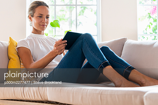 Concentrated woman at home relaxing on couch and looking at tablet - p300m2277477 von Steve Brookland