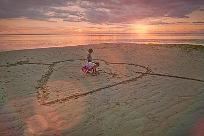 Boy and girl brother and sister drawing heart-shape in sand on tranquil sunset beach - p1023m1446538 by Tom Merton