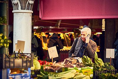 Mann telefoniert auf dem Markt i - p1312m2082207 von Axel Killian