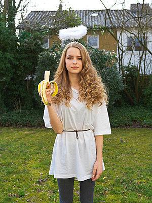 Girl holding banana - p1376m2065717 by Melanie Haberkorn