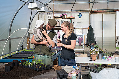 Family in greenhouse - p312m2139759 by Viktor Holm