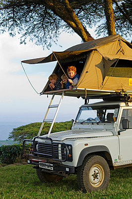 Camping overland style with a roof tent fitted to a safari landrover beneath majestic Acacia abyssinica trees at a tea plantation - p6521868 by John Warburton-Lee