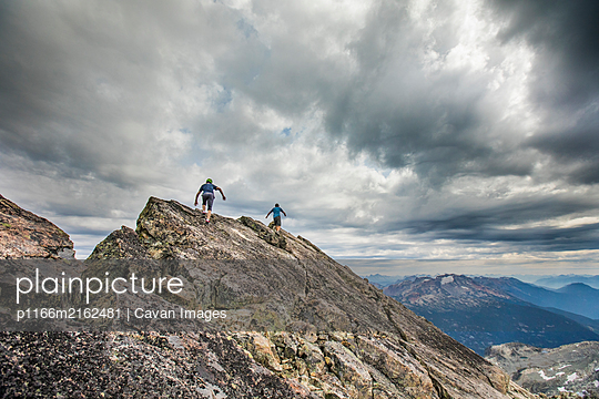 Two climbers approach the summit of a mountain peak. - p1166m2162481 by Cavan Images