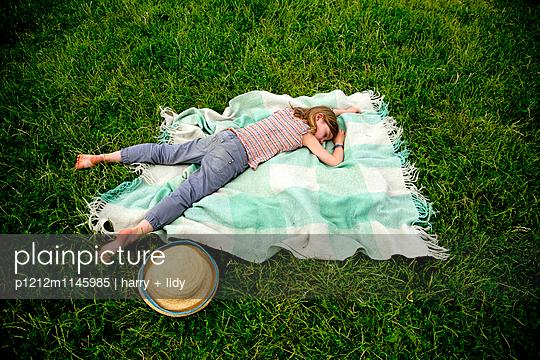 Mädchen schläft auf der Decke im Garten - p1212m1145985 von harry + lidy