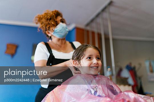 Mature female hairdresser with cute customer at hair salon during COVID-19 - p300m2242448 by Ezequiel Giménez