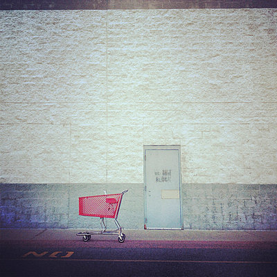 Empty shopping cart on road by building - p1166m1152076 by Cavan Images