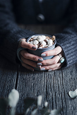 Cropped image of woman holding mug of hot chocolate topped with marshmallows at wooden table - p1166m1415179 by Cavan Images