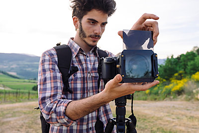 Young male photographer inserting glass in digital camera lens on field - p1166m1542289 by Cavan Social