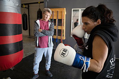 Trainer watching female boxer using punching bag in gym - p1192m2033872 by Hero Images