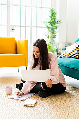 Smiling young woman writing in note pad while sitting with coffee cup on carpet against sofa at loft apartment - p300m2225790 by Giorgio Fochesato