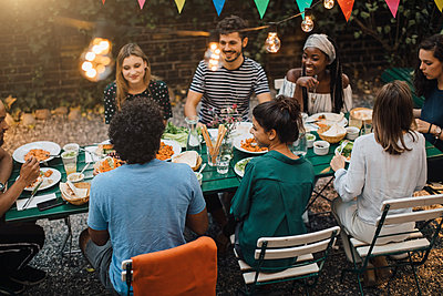 High angle view of multi-ethnic young friends enjoying dinner at table during garden party - p426m2046165 by Maskot