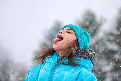 Girl looking up, sticking out tongue catching snowflakes - p429m1103133 by Rebecca Nelson