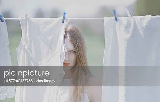 Young blond woman outdoors behind the drying linen - p1577m2157786 by zhenikeyev