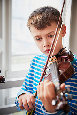Boy playing violin during a lesson - p300m2189465 by Phillip Waterman