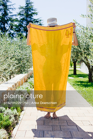 Girl behind yellow bath towel - p1621m2291753 by Anke Doerschlen