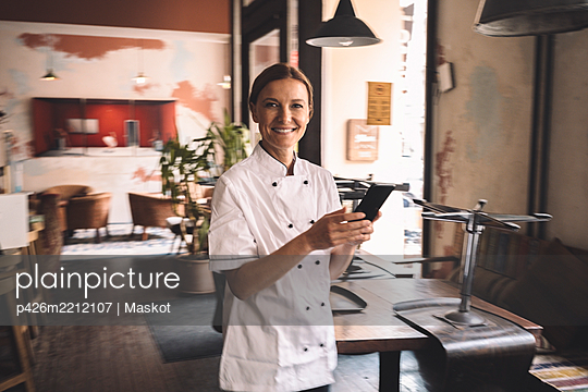 Portrait of smiling chef with smart phone in restaurant - p426m2212107 by Maskot