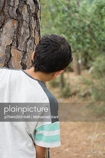 Rückansicht eines Jungen hinter einem Baum - p794m2031648 von Mohamad Itani