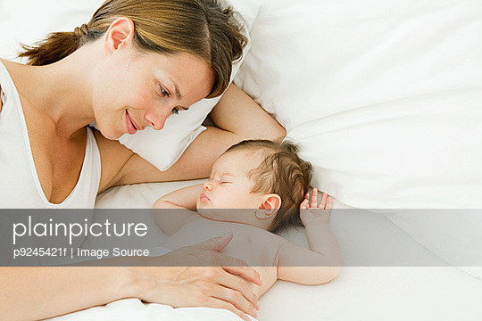 Mother watching baby sleep - p9245421f by Image Source