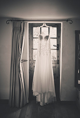 wedding dress hanging by a door - p1072m993597 by Neville Mountford-Hoare