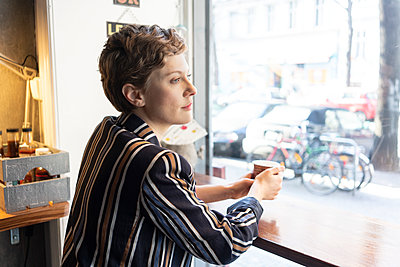 Pensive freelancer in a coffee shop looking out of window - p300m2203125 by A. Tamboly