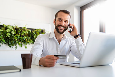 Smiling businessman with credit card and laptop talking on mobile phone at office - p300m2264891 by Daniel Ingold