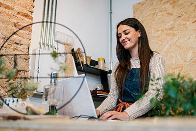 Smiling beautiful female owner using laptop in florist's shop - p300m2274937 by Ezequiel Giménez