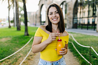Smiling young woman holding orange juice bottle while standing in park - p300m2294260 by Xavier Lorenzo