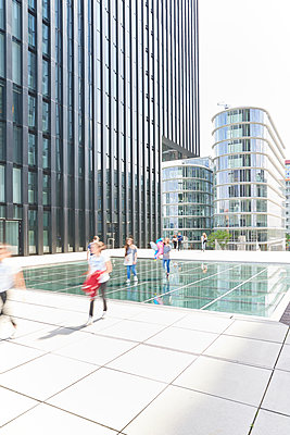 Pedestrians passing modern office buildings - p587m1155111 by Spitta + Hellwig