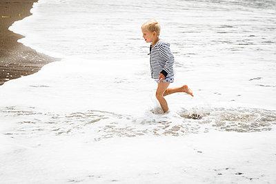 Blonde boy splashing around in water - p756m1496076 by Bénédicte Lassalle