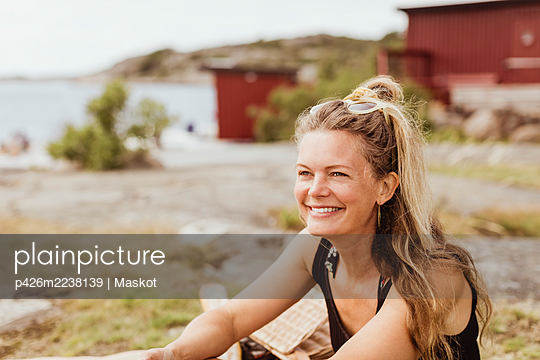 Smiling woman looking away during picnic at harbor - p426m2238139 by Maskot