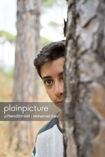 Ängstlicher Junge hinter einem Baum - p794m2031649 von Mohamad Itani