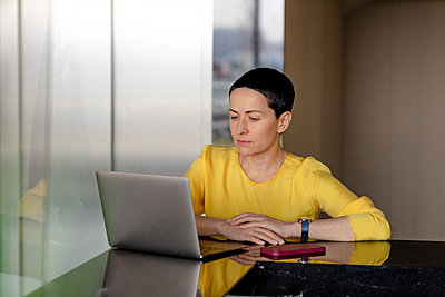 Serious female entrepreneur looking at laptop in office - p300m2276986 by Oxana Guryanova