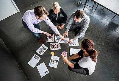 High angle view of business colleagues working with photographs in office - p426m811564f by Maskot