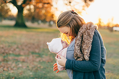Mother and baby daughter outdoors, mother carrying baby in baby sling - p429m1557482 by Katie Rollings
