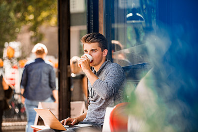 Young man drinking coffee and using laptop at cafe - p429m2075314 by Tom Dunkley