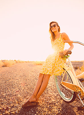 Hispanic woman leaning on bicycle on dirt road - p555m1311886 by Dave and Les Jacobs