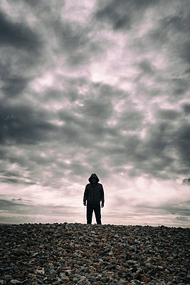 Man in hooded jacket standing on shingle beach looking at camera - p597m2133989 by Tim Robinson