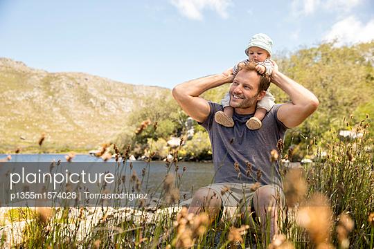 Vater und Baby am Seeufer - p1355m1574028 von Tomasrodriguez